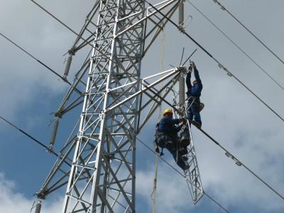 Operaris canviant els suports d'una línia elèctrica