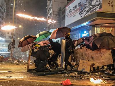 Diversos manifestants es protegeixen amb paraigües i altres objectes durant les protestes a Hong Kong, el 18 de novembre de 2019