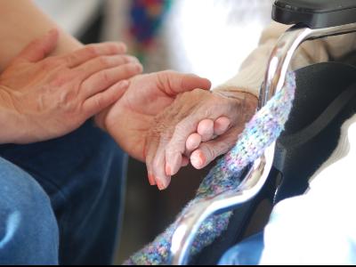 Un cuidador agafa la mà d'una persona gran