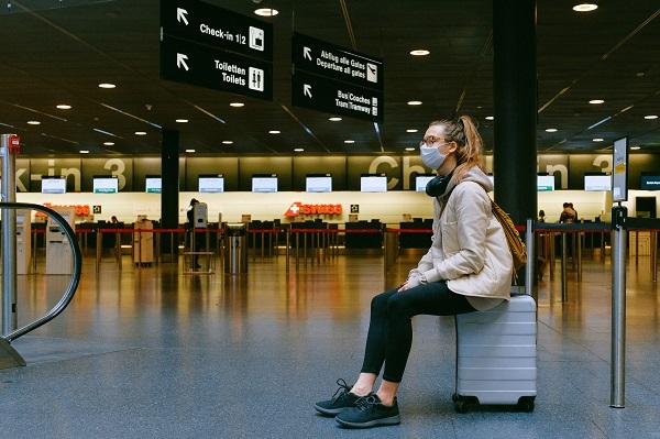 Una dona amb mascareta espera en un aeroport.