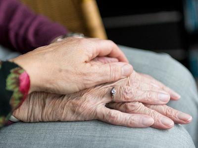 Mans d'una persona gran i una persona cuidadora