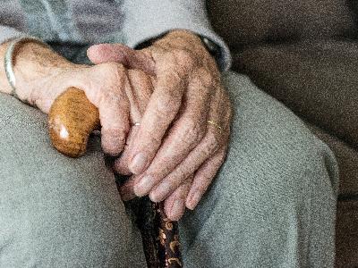 Mans d'una persona gran recolzades en un bastó