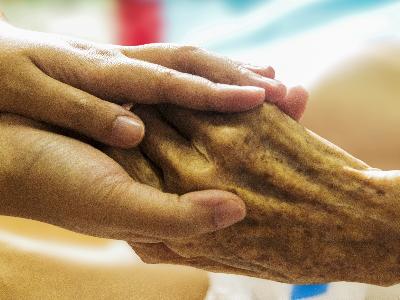 Les mans d'una persona cuidadora agafen les d'una usuària de residència